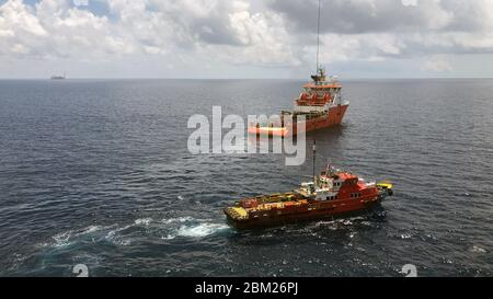 Balikpapan, Indonesia - October 2019: Offshore supply vessel and offshore crew boat on an oil field, cargo operations undergo
