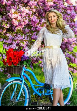 girl carry flowers in retro bicycle. spring beautiful woman in dress. girl vintage bike. blooming sakura tree. summer fashion and beauty. lady walk in park. pink cherry tree blossom. Amazing summer.