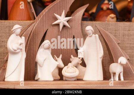 Christmas wooden figurines.Christmas nativity scene wooden figurines inside a wooden house representing the holy family. - Stock Photo