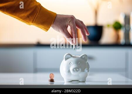 Personal finances, woman putting money into a piggy bank- -wealth and financial concept. White piggy bank in the foreground.