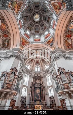 Feb 4, 2020 - Salzburg, Austria: Upward angle of central dome ceiling mural paintings and organ pipe over pews in the nave of Salzburg Cathedral - Stock Photo