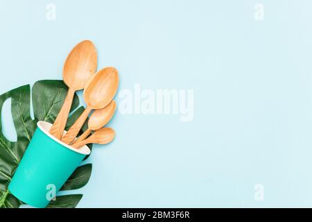 Tableware wooden spoons in a paper Cup and green leaf on blue background, top view. Zero waste, environmentally friendly concept. - Stock Photo