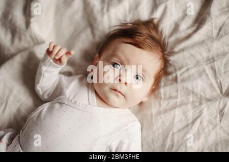 Closeup portrait of cute Caucasian newborn baby. Adorable funny child infant with blue grey eyes and red hair lying on bed looking at camera.