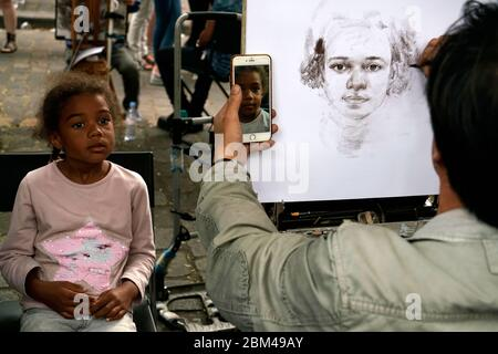 Artist sketching a portrait for a young girl in Place du Tertre in Montmartre.Paris.France - Stock Photo