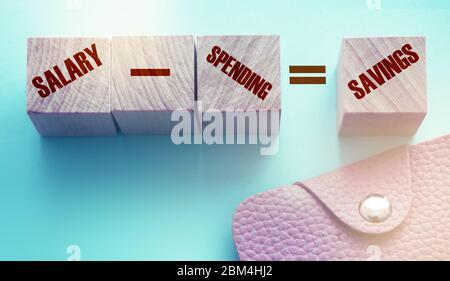 Salary minus spending equal to savings text on wooden cubes with leather wallet on light blue background. Personal Money concept