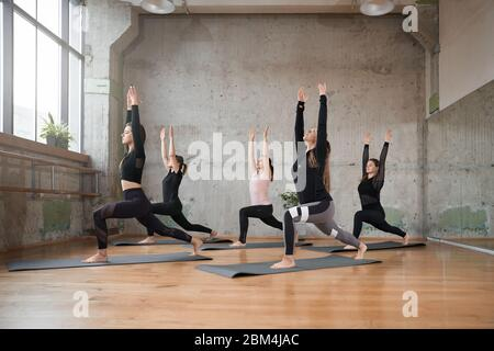 group of five girls practicing yoga in fitness hall doing