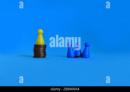 Pawns standing on piles of different sizes of coins. Income and economic inequality concept.