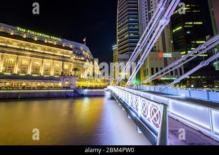Singapore 30. December 2019 : Cavenagh Bridge at night, in the background The Fullerton Hotel - Stock Photo