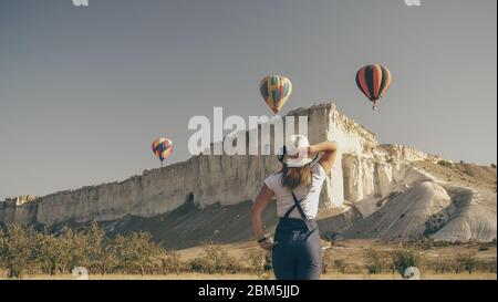 a girl in simple rural clothes and a hat raised her head and looks at the sky. there in the sky over a white rock at dawn, hot air balloons take off C - Stock Photo