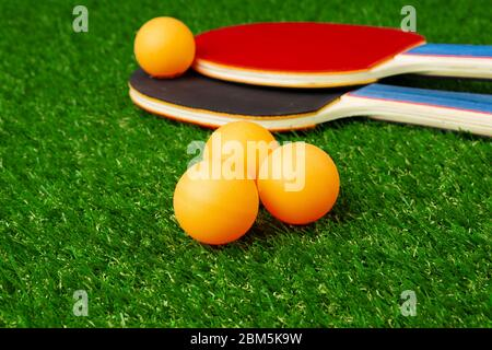 Ping pong rackets and ball on grass - Stock Photo