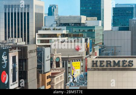 High angle view of buildings and skyscrapers in the Tokyo Ginza district with the famous Wakō clock in the center and Hermes's rider in the foreground - Stock Photo
