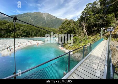 Clear, turquoise blue pools and swing bridge in the Makarora River in Mount Aspiring National Park, New Zealand - Stock Photo