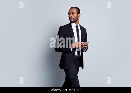 Portrait of confident smart afro american agent company representative wait business partner use smartphone type message wear blazer jacket suit tux - Stock Photo