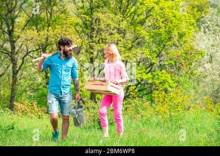 A pair of farms carries boxes with vegetables and greens along the field. Couple Gardener. Portrait of wife and husband while working in garden. Wife