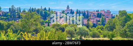 Observe the panorama of Alhambra fortress with towers, ramparts, Alcazaba and Santa Maria Church, surrounded by lush greenery, Granada, Spain - Stock Photo