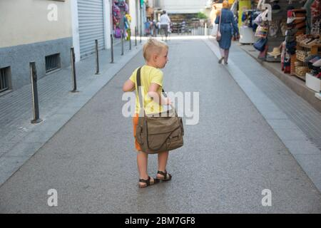 Little boy with blond hair walking on the street in summer sunny day with big bag. Travel in Spain. - Stock Photo