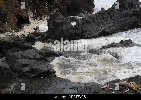 Palikea stream running through volcanic rock and flowing into the Pacific Ocean at the Oheo Gulch in Hana, Maui, Hawaii, USA
