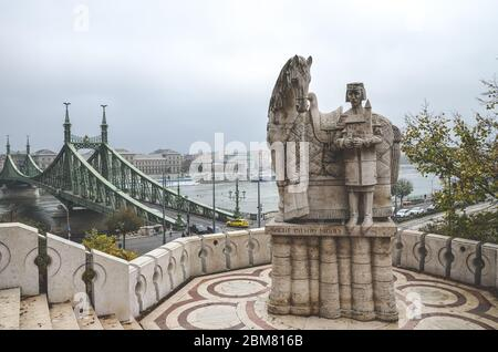Budapest, Hungary - Nov 6, 2019: Szent Istvan Kiraly, Saint Stephen statue on the Gellert Hill. The city with Liberty Bridge over the Danube river in the background. Sculpture. Horizontal photo. - Stock Photo