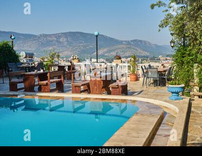 Table and chairs in empty cafe next to the pool, Turkey - Stock Photo