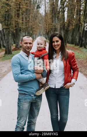 Happy family woman and man with 1 year old boy outdoors in park - Stock Photo