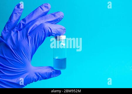 Vial with cure Covid-19. Doctor, nurse or scientist hand in blue gloves holds a vaccine coronavirus - Stock Photo