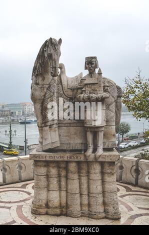 Budapest, Hungary - Nov 6, 2019: Szent Istvan Kiraly, Saint Stephen statue on the Gellert Hill. The city along the Danube river in the background. Sculpture. Vertical photo. - Stock Photo