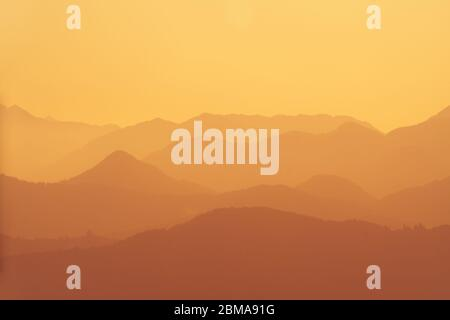Beautiful orange layers of hills and mountains during sunset in Slovenia. Tourism, hiking, nature, environment and forestry concepts. - Stock Photo