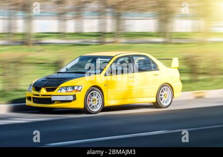 Yellow sports city car at high speed road - Stock Photo