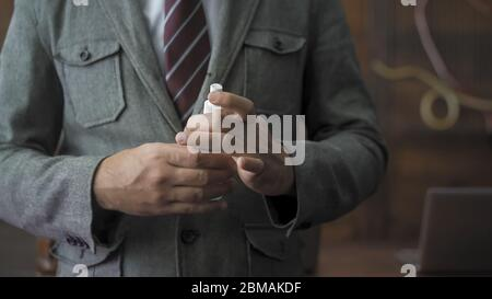 Businessman holding a sanitizer or antiseptic liquid. Close up of business man's hands with bottle of antiseptic which need to be used due to pandemic - Stock Photo
