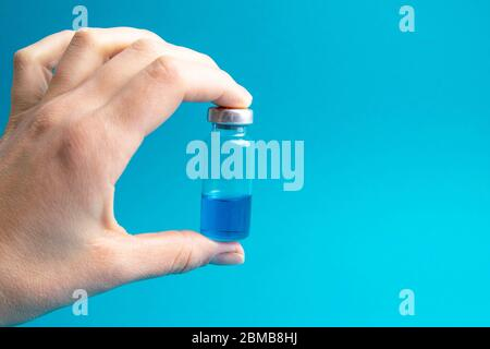 Vial with cure Covid-19. Doctor, nurse or scientist hand holds a vaccine coronavirus - Stock Photo
