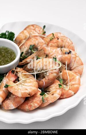 fresh boiled prawns with zesty citrus dipping sauce on white table - Stock Photo