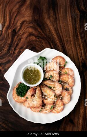 fresh boiled prawns with zesty citrus dipping sauce on wood table - Stock Photo