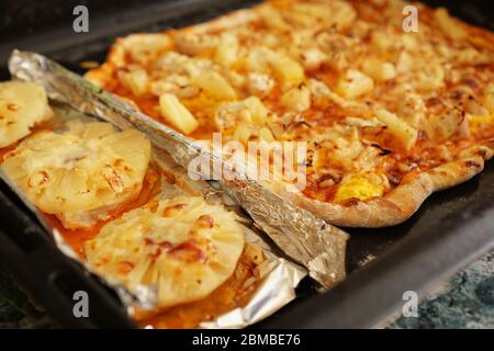 Chicken fillet with pineapples on foil and homemade Hawaiian pizza. Simple homemade recipes with pineapple - Stock Photo
