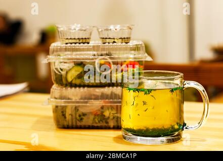 Mug with hot broth and herbs on a wooden table. Against the background of transparent disposable containers with a salad of tomatoes and cucumbers. Bl - Stock Photo