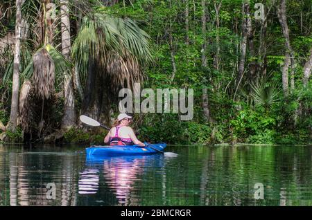 An active senior woman kayaks on the Silver River in Silver Springs State Park, Florida - Stock Photo