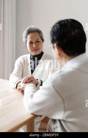 An Asian elderly couple sitting at the table - Stock Photo