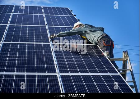 Professional electrician standing on ladder and installing photovoltaic solar panel system. Man technician in safety helmet under blue sky. Concept of alternative energy and power