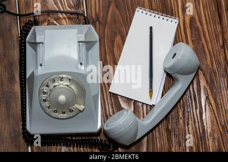 vintage grey phone, writing pad on wooden background close-up, top view. - Stock Photo