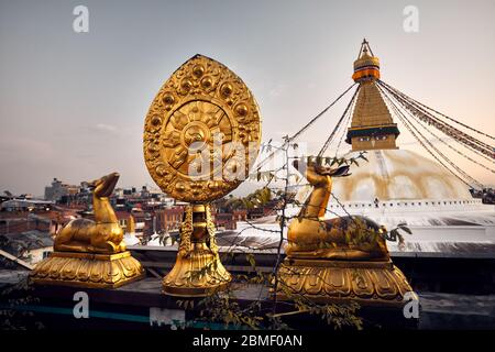 Golden deer statues with leaf at the roof of monastery and Bodnath Buddhist Stupa at sunset sky in Kathmandu - Stock Photo