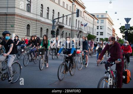 Ljubljana, Slovenia, May 8, 2020: Protesters wearing face masks as preventive measure ride their bicycles  during an anti-government protest amid the coronavirus crisis. Following whistleblower's revelations of corruption in the government of Janez Janša and accusations of its undemocratic rule over five thousand people rode bicycles around government buildings in sign of protest. - Stock Photo