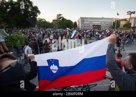 Ljubljana, Slovenia, May 8, 2020: Protesters hold up a Slovenian flag as thousands ride their bicycles in front of the parliament building during an anti-government protest amid the coronavirus crisis. Following whistleblower's revelations of corruption in the government of Janez Janša and accusations of its undemocratic rule over five thousand people rode bicycles around government buildings in sign of protest. - Stock Photo