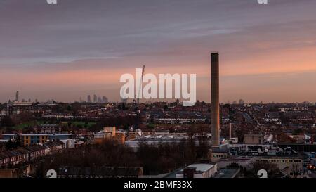 London, England, UK - January 2, 2013: The sun rises over the suburban streets of Tooting, South London, with the city skyline in the distance. - Stock Photo