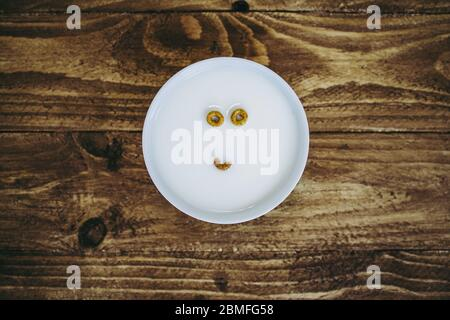 A bowl with just two and a half pieces of round cereal left creating the appearance of a face in the milk - Stock Photo