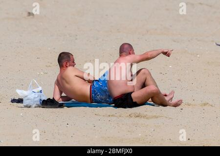 Weymouth, Dorset, UK.  9th May 2020.  UK Weather:  Two men sunbathing on the beach on a day of scorching hot sunshine at the seaside resort of Weymouth in Dorset during the coronavirus lockdown.  Picture Credit: Graham Hunt/Alamy Live News