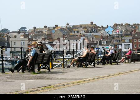 Weymouth, Dorset, UK.  9th May 2020.  UK Weather:  People sitting next to the harbour on a day of scorching hot sunshine at the seaside resort of Weymouth in Dorset during the coronavirus lockdown.  Picture Credit: Graham Hunt/Alamy Live News