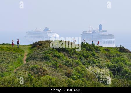 Weymouth, Dorset, UK.  9th May 2020.  UK Weather:   Walkers on the cliff top on the South West Coast Path with a view of the five cruise ships anchored in the bay off the coast of the seaside resort of Weymouth in Dorset on a hot sunny day due to the cruising industry shutting down during the coronavirus lockdown.  There are four P&O ships which are The Oceana, Aurora, Arcadia and Ventura and one Cunard ship the liner Queen Mary 2.  (Oceana and Arcadia pictured) Picture Credit: Graham Hunt/Alamy Live News