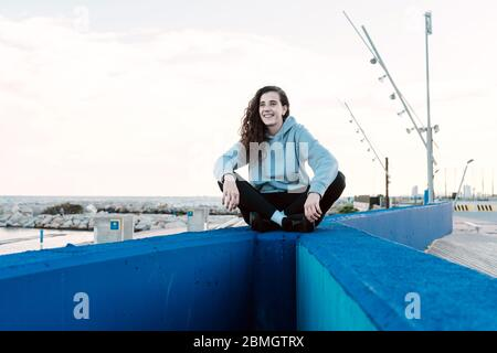 Young teenager sitting on a stone wall with her legs crossed while smiling