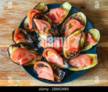 top view of fried sliced eggplants with spice dip and fresh slices of tomatoes on black plate on shabby wooden table at home kitchen - Stock Photo