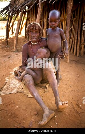 Grandmother Gado sitting on a hide together with her two grandchildren Aike and Zubo(upright) in front of their hut in Kaina.