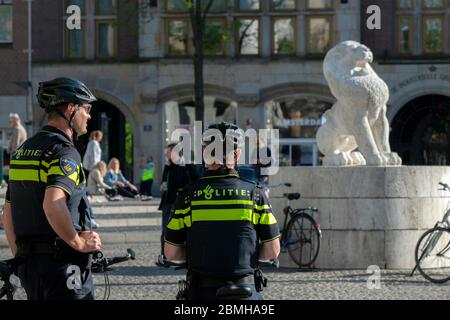 Police Patrolling On The Dam Square During The Corona Virus Outbreak At Amsterdam The Netherlands 2020 - Stock Photo
